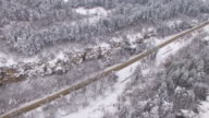 4K Drone view of snow forest and a road