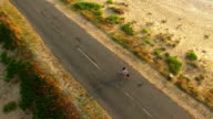4K Drone view of Woman cycling on sunny road