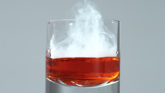 dropping smoky dry ice in a glass with liquor / slow motion