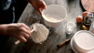Dropping the egg into the flour