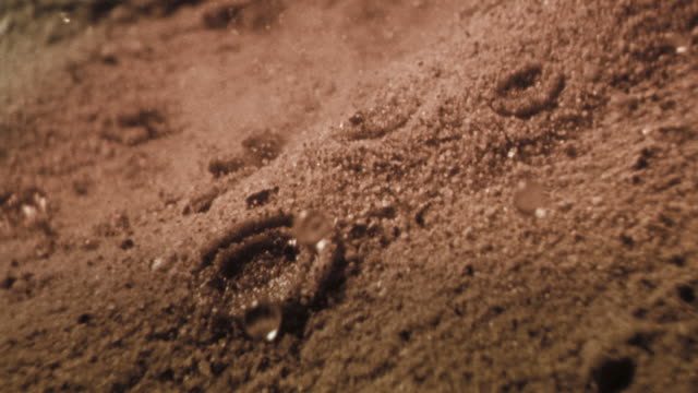 Drops of rain splash into dry desert sand. Available in HD.