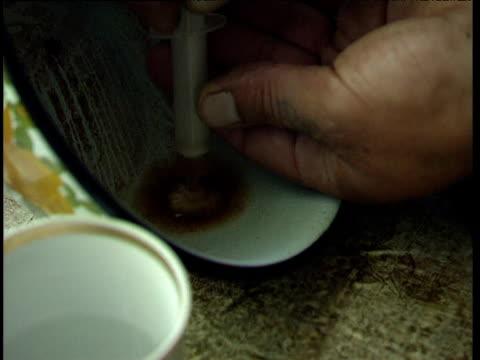 Drug addict fills syringe with prepared heroin liquid through cotton wool bud filter Tajikistan