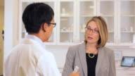 MS Drug Sales Rep Holding Pills, Talking to Pharmacist / Richmond, Virginia, USA
