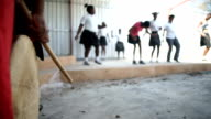 CU drum being played whilst African ethnicity children dance in the background/ KwaZulu-Natal/ South Africa