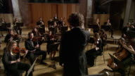 MS ZO Drummer and musicians performing in orchestra, conductor leading / London, United Kingdom