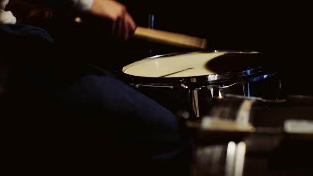 Schlagzeuger spielen sein Schlagzeug auf schwarzem Hintergrund