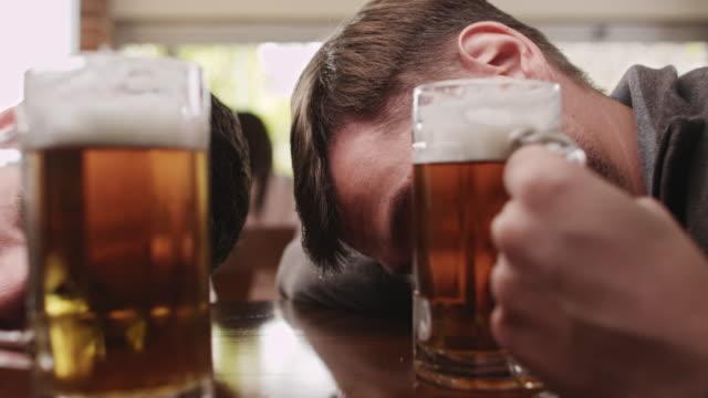 Drunk friends sleeping in a bar