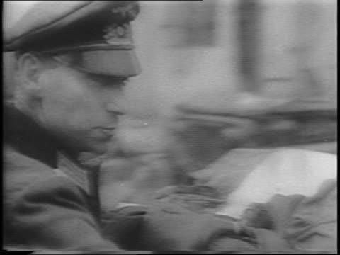 Drunk German soldier talking to American GI / closeup on drunken German soldier swaying and talking / smoke rising over city of SaintMalo / German...