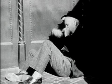 1949 B/W MONTAGE Drunk man lying on pavement / USA / AUDIO