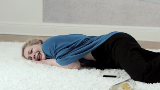 Drunk woman cries while laying on a rug.