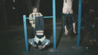 Drunk young people hanging upside down on playground bars