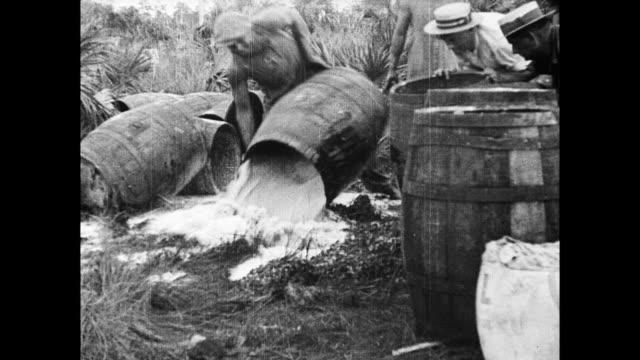 Dry Idaho senator William Borah discusses Prohibition / black bartender serves laughing smoking white men in bar / men pushing over barrels in the...