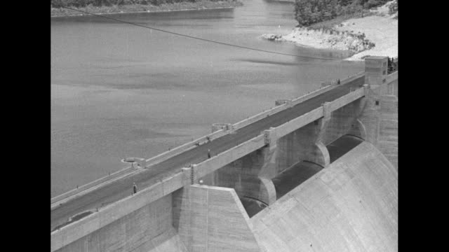 VS dry inclines of Norris Dam with lake behind / VS water shooting out of spillway / electrical facility with transmission lines / Note exact day not...