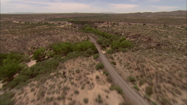 AERIAL Dry riverbed with older bridges and railroad track in New Mexico desert near Demming, New Mexico, USA