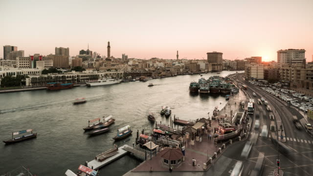 Dubai Creek at dusk with passing traffic and boats