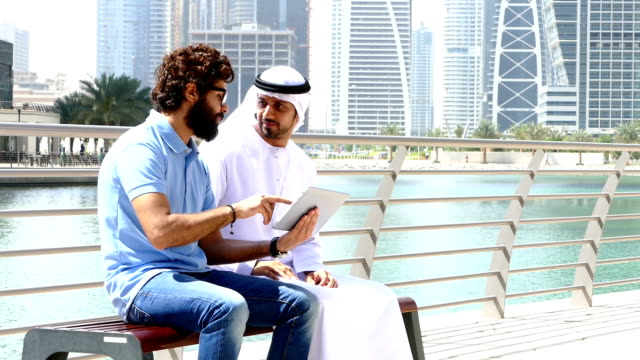 Dubai - Young people using digital tablet in the city
