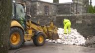 Dumfries EXT GVs Sandbags being loaded beside swollen river / workers piling up sandbags
