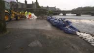 Dumfries flood defences Workers making sandbag wall beside river / Digger unloading bags