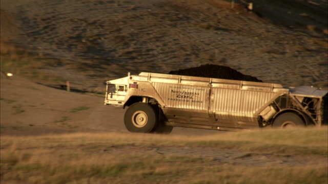 A dump truck carries a load of coal along a field in Beulah, North Dakota. Available in HD