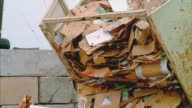 CU PAN Dump truck dropping cardboard onto pile, Santa Barbara, California, USA
