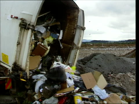 Dump truck dumping garbage including electronic waste / United Kingdom