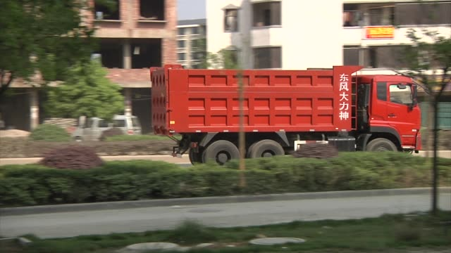 Dump truck with Chinese signage driving by / truck filled with gravel driving by / construction vehicles and equipment parked in lot / backhoes /...