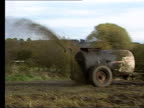 Dung powered fire station LIB Tractor along through field towing muck spreader as spraying manure