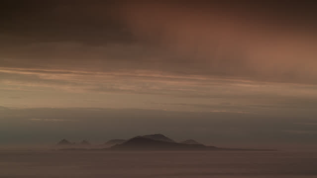 Dusk falls over misty sea and islands, Falkland Islands