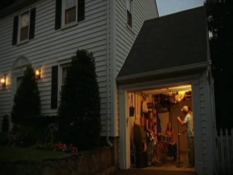 Dusk in a suburban street. A longshot pans right along the side of a white house and comes to rest on the garage. Inside a teenage rock band can be seen rehearsing. A guitarist, a drummer and a baseball cap wearing singer.  Long Island, New York, USA