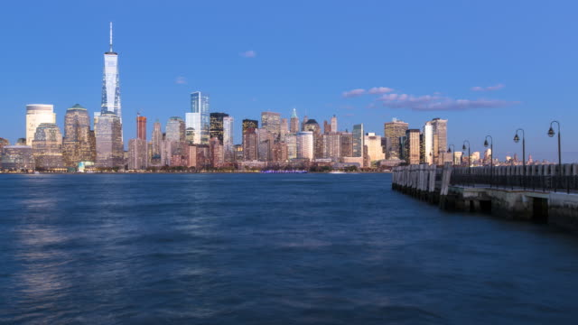 Dusk to night Time lapse of One World Trade Center and Downtown Manhattan viewed across the Hudson River, New York, Manhattan, United States of America