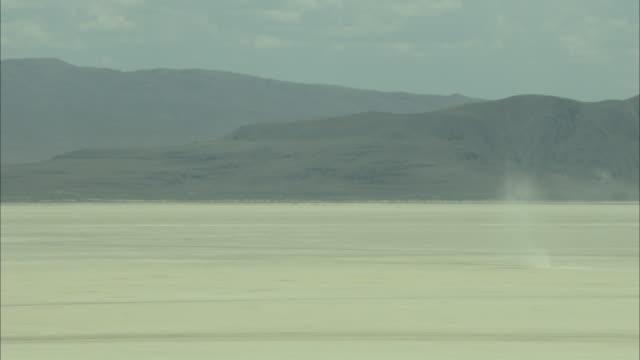 Dust devil leaves wispy trail across desert floor