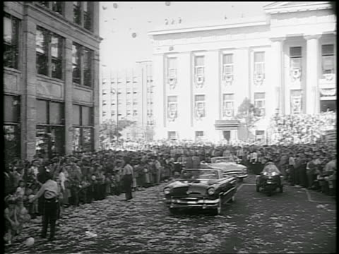 Dwight D Eisenhower stands in moving convertible in ticker tape parade on city street