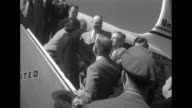 Dwight D Eisenhower steps out door of United airplane marked 'Eisenhower Special' and is greeted by local Republican Party officials on steps he...