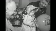 Dwight Eisenhower holds a baby girl on his lap as Mamie Eisenhower holding an 'I Like Ike' balloon stands nearby they coo over the baby who wears an...