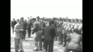 Dwight Eisenhower US Army Chief of Staff climbs down ladder from US Army Air Forces plane on airfield and is greeted by officials / US and Chinese...