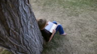 Dynamic Shot of boy reading book by tree