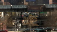 Dynamic shot of cars driving over traffic on the cross bronx expressway on an overpass as well as a train passing on a grungy train line overhead in the bronx during the day