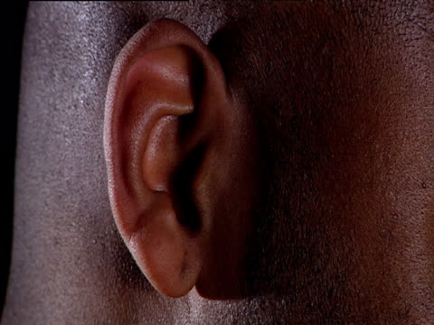 Ear belonging to man with shaved head