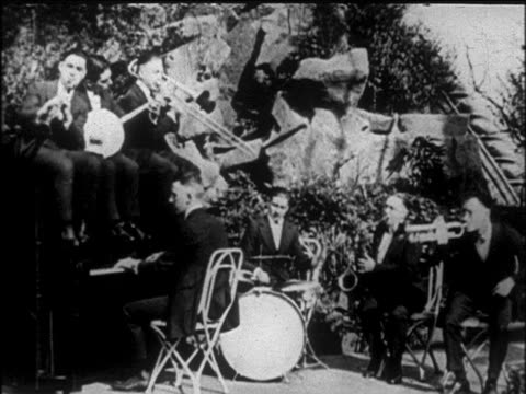B/W early 1920s Tokyo Five jazz band playing on roof as Pat Rooney II dances in foreground / NYC / newsreel