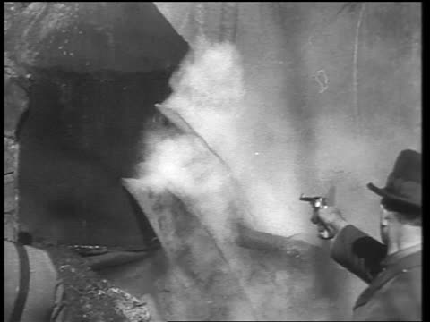 B/W early 1930s man shooting holes in outdoor distilery with pistol / liquor pours out