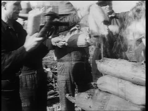 B/W early 1930s men smashing liquor bottles with hammers smiling for camera