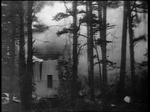 B/W early 1930s small wooden building exploding in forest