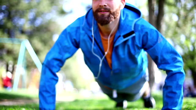 Early 30's bearded man exercising in park.