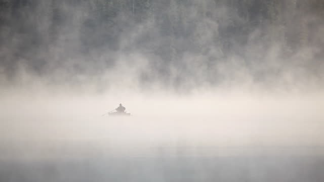 HD early morning fishing on lake in fog