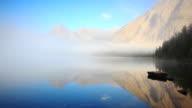 Primo mattino di nebbia crescente dal lago superficie con montagne Raggiante