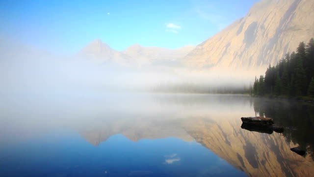 Early morning mist rising from lake surface with mountains glowing