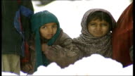 Victims suffer in winter weather PAKISTAN EXT People walking along snow covered narrow mountain track BV Rivers along track MS People looking on MS...