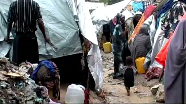 AlShabaab maintains ban on western aid agencies EXT People stand amongst makeshift tents in temporary refugee camp Refugee camp worker organising...