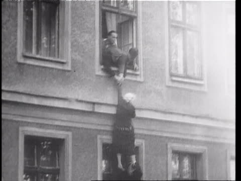 East Berlin guards try to pull woman into window as West Berliners pull her to ground / person on window ledge of building on border of East and West...