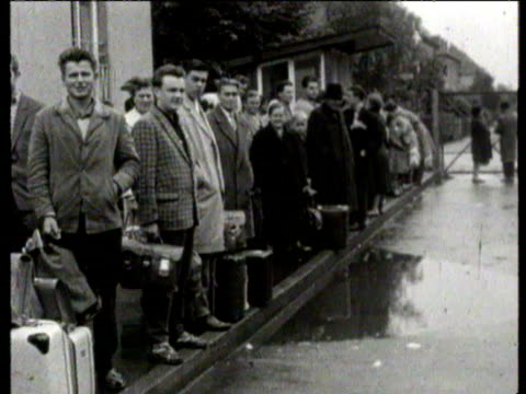 East German refugees of all ages queue and wait in rain after East Germany moves to close the border Willy Brandt the Mayor of West Berlin walking...